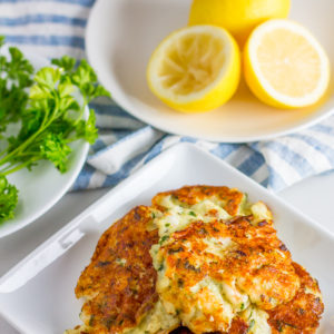 plate of lemon, plate of parsley, plate of low carb shrimp cakes with a stripped blue and white towel
