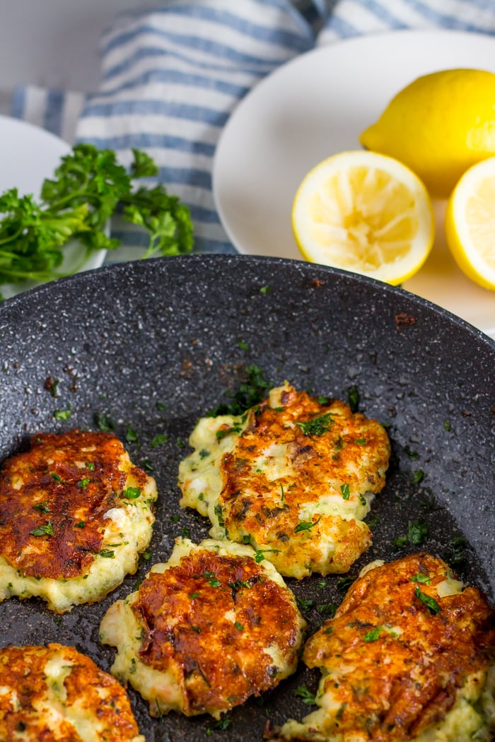 low carb shrimp cakes in a grey pan with a dish of lemon and parsley on the side on top of a blue and white striped towel