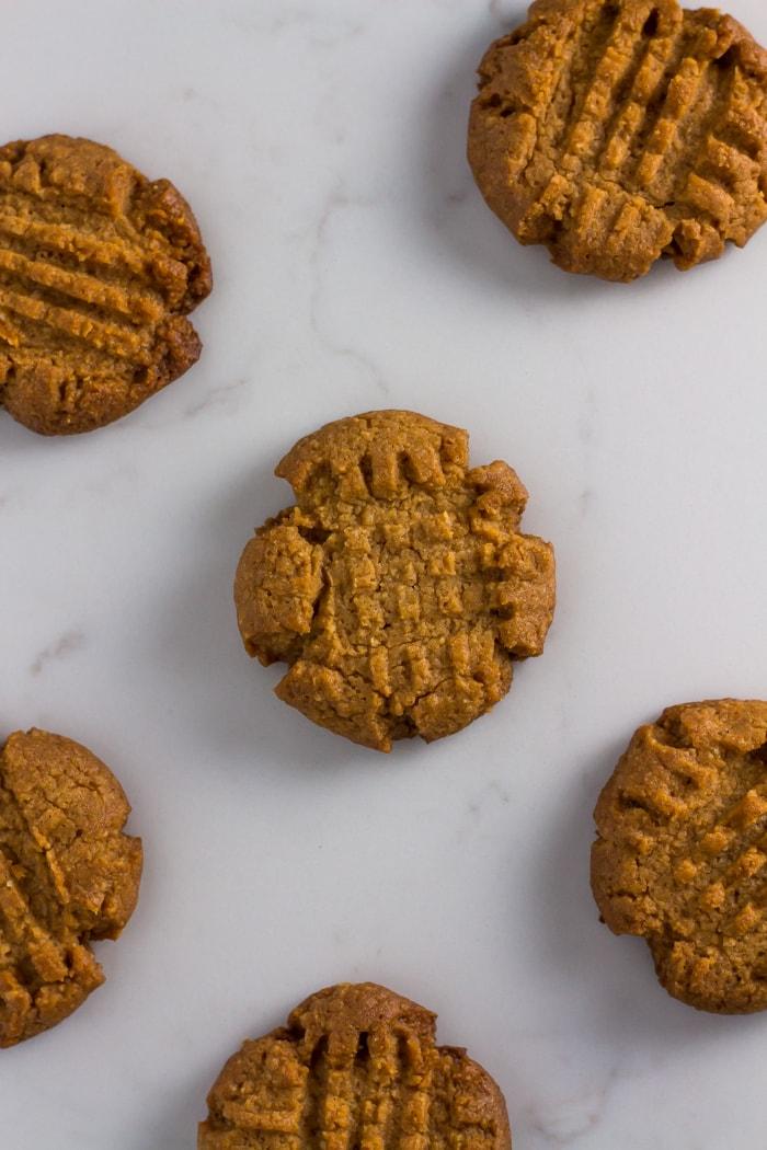 six keto peanut butter cookies spread across marble slate