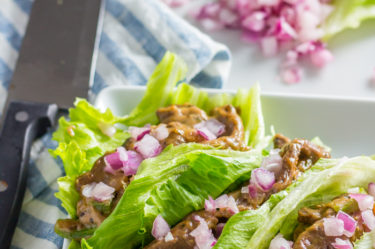 three lettuce wraps with onion, green peppers and lettuce