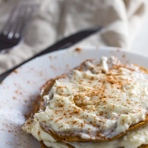 pumpkin spice keto pancakes topped with cream cheese and pumpkin spice sprinkle