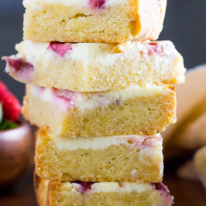 stack of chewy cheesecake keto blondies with berries