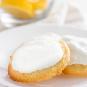 Lemon keto cookies on a plate with a bowl of lemons in the background