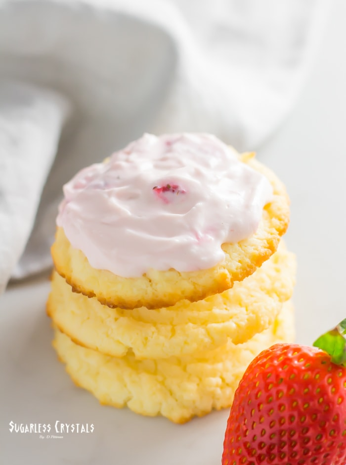 Cream cheese cookies with a strawberries and cream icing stacked on one another with strawberry on the side
