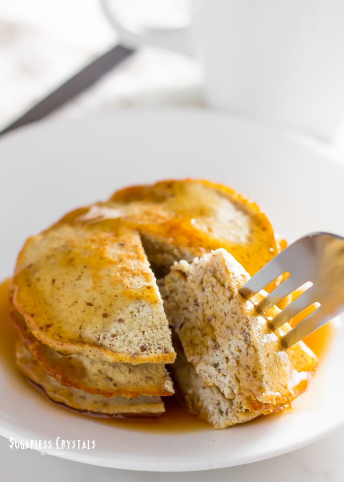 Coconut flour pancakes with sugar free maple syrup being eaten