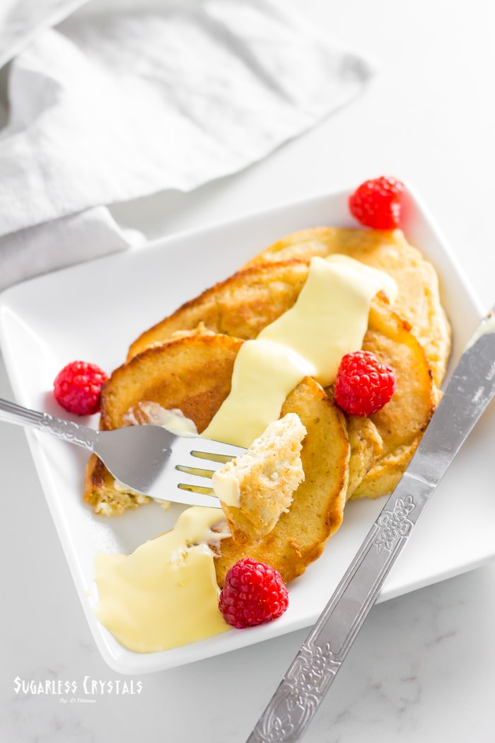 Spiced almond flour pancakes with vanilla custard topping with sides of raspberries