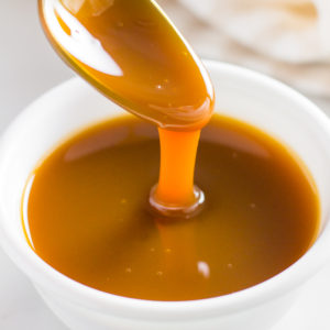 Keto caramel sauce in bowl with spoon