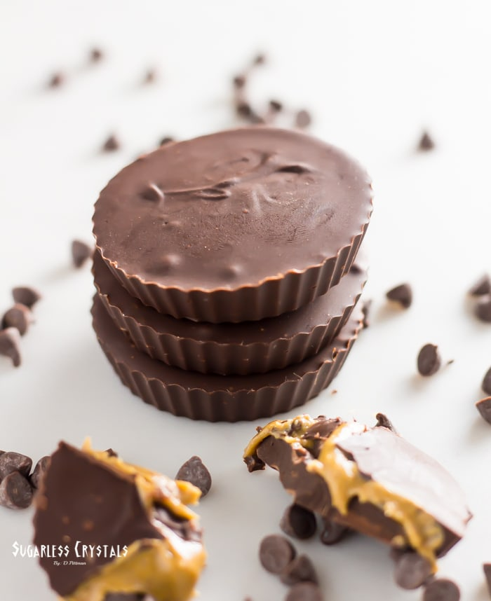 Keto peanut butter cups stacked with one broken in half showing peanut butter