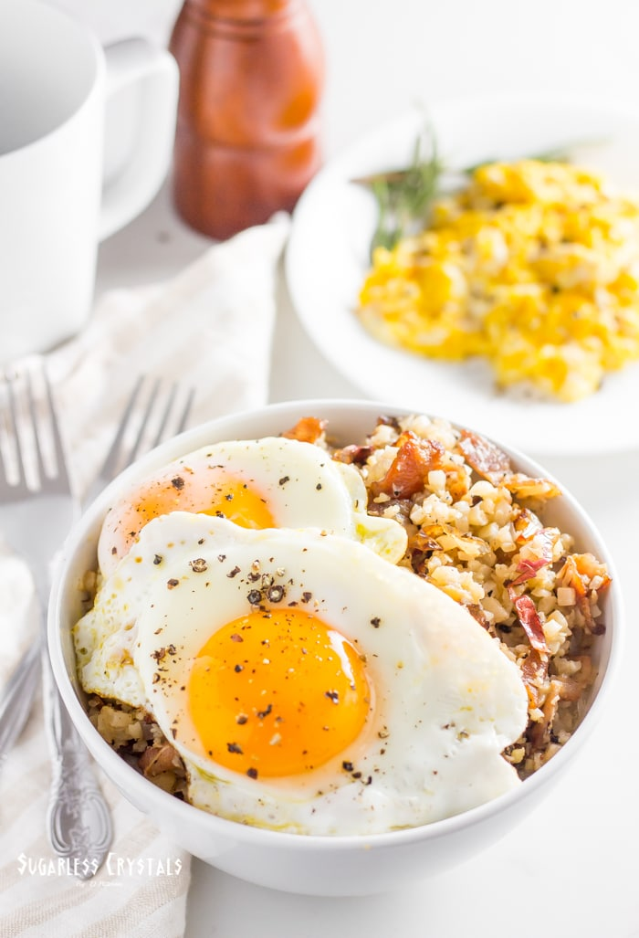 keto bacon and egg breakfast bowl with scramble eggs and sunny side up