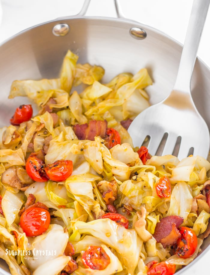 cabbage and bacon recipe with cherry tomatoes in stainless steel frying pan