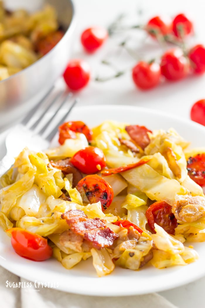 cabbage and bacon recipe with tomatoes on a plate with fork