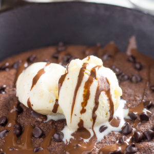 skillet keto cookie recipe with chocolate chips, ice cream and covered in chocolate sauce
