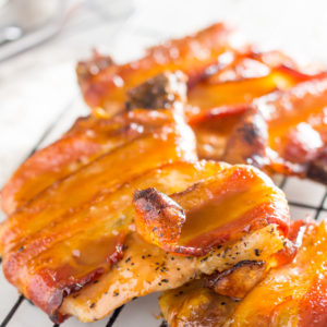 bacon wrapped pork chops out of the oven and glazed with caramel