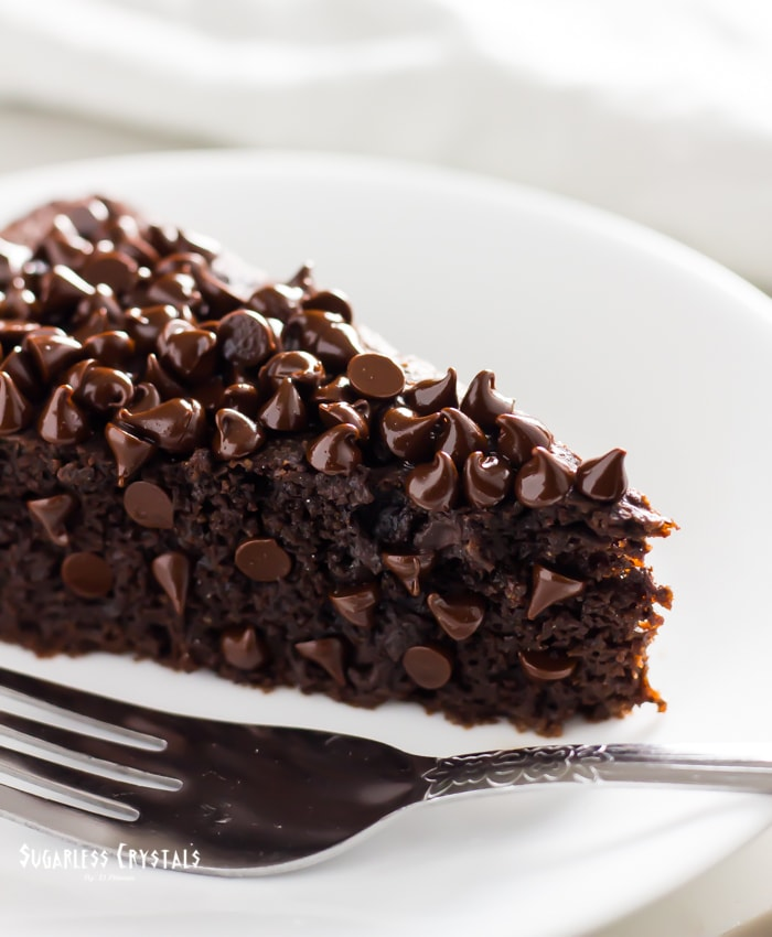 keto chocolate cake with melted chocolate chips on a plate with fork