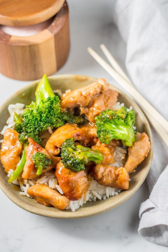 chicken broccoli stir fry on top of rice with chopsticks