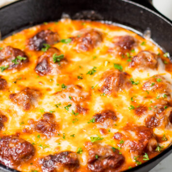 keto meatballs with cheese baked in a cast iron skillet